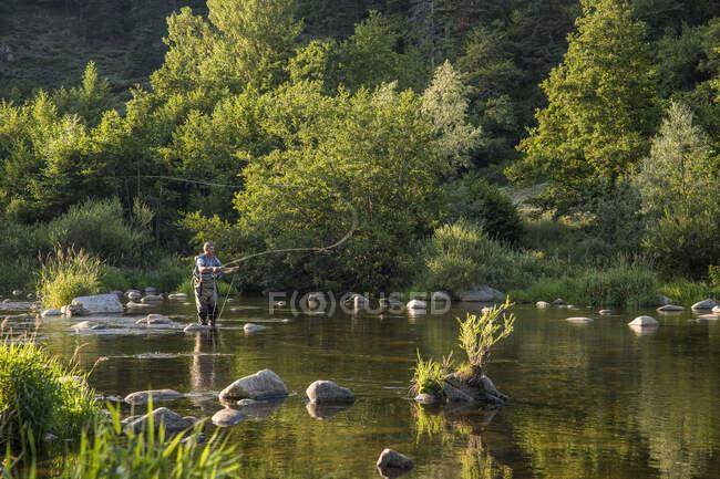 Auvergne, Rodano-Alpi, Alta Loira, Pesca a mosca nella valle dell'Alta Loira. Un pescatore che getta la sua canna da pesca. — Foto stock