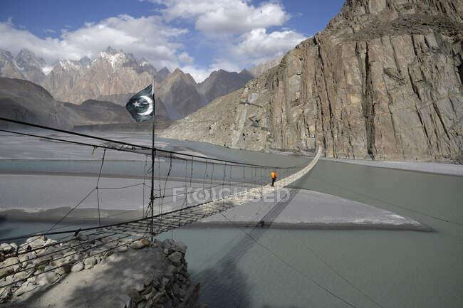 Pakistan, région de Gilgit Baltistan, Passu, un homme traverse la rivière Hunza sur le pont suspendu Hosseini en face des montagnes du Karakoram — Photo de stock
