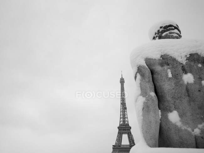 France, Paris, 16th arrondissement, snowy statue of man at Trocadero turns towards the Eiffel tower / Snow covered man statue facing Eiffel tower, 16th arrondissement, Paris, France — стоковое фото