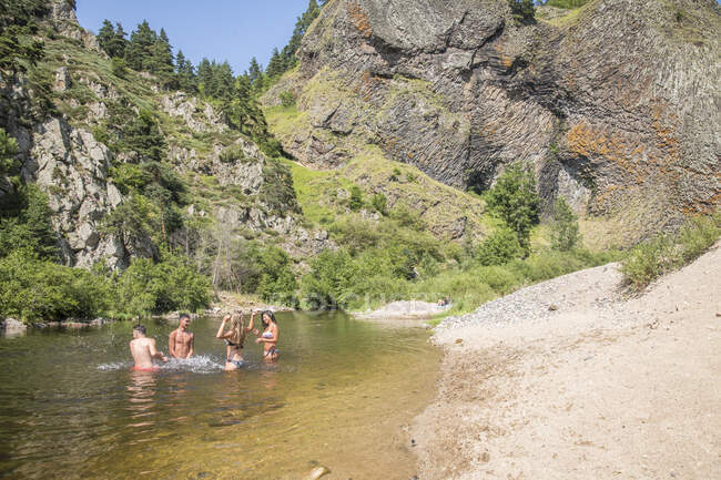 Auvergne, Rhone-Alpes, Haute-Loire en Arlemdes bajo los acantilados de basalto. Cuatro fibras están bañándose en el río.. - foto de stock