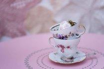 Empilé des tasses en porcelaine vintage avec oeuf de Pâques sur table rose — Photo de stock