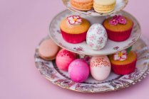Decorated easter eggs with macarons and muffins on plates etagere on pink background — Stock Photo
