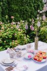 Setting table with decorated muffins and easter painted eggs in spring garden — Stock Photo