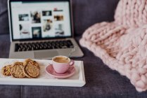 Tray with coffee and chocolate cookies in front of open laptop on couch — Stock Photo