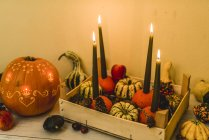 Autumnal decoration with pumpkins with lit candles — Stock Photo