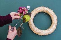 Primer plano de manos de artesano mujer Decoración guirnalda con flores de Hortensia - foto de stock