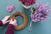 Close-up of female craftsperson hands making autumnal decoration of willow wreath and heather flowers — Stock Photo