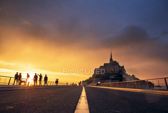 Tourists on road to ancient abbey at sunset, Le Mont-Saint-Michel, France — Stock Photo