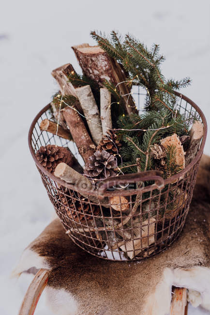 Sledge with fur and basket of firewood and fairy lights — Stock Photo