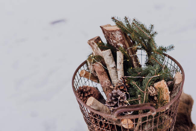 Basket of firewood and fairy lights outdoors on snow — Stock Photo