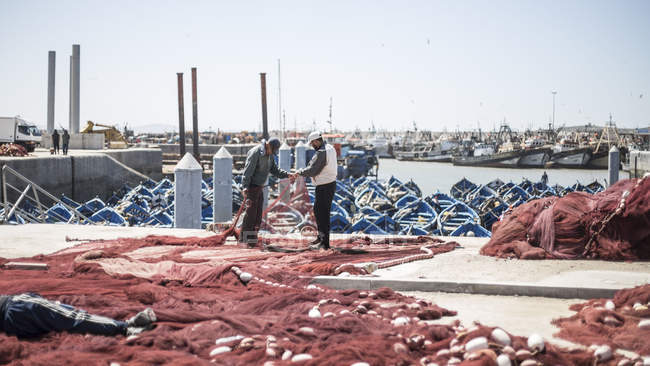 Ships and people in fishing harbor of coastal port Essaouira, Morocco — Stock Photo