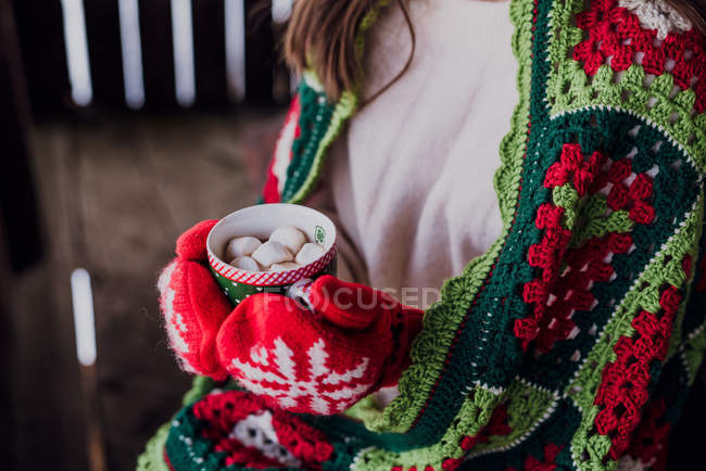 Cropped view of woman wrapped in winter blanket holding cup of hot cocoa with marshmallows in mittens. — Stock Photo