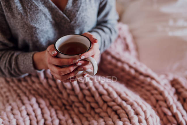 Cropped view of woman sitting in bed under knitted blanket with cup of tea, detail — Stock Photo