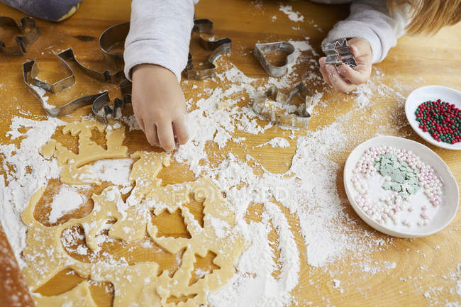 Cropped view of little girl cutting Christmas cookies dough with cutters. — Stock Photo