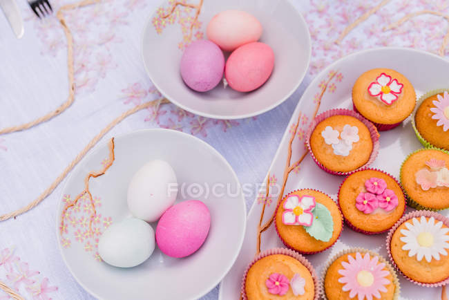 Украшены кексы и Окрашенные пасхальные яйца на столе — стоковое фото