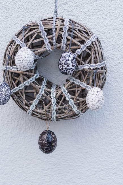 Wooden wreath with Easter eggs on lace in grey tones — Stock Photo