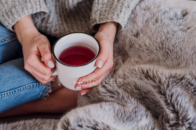 Cropped view of woman with cup of hot black tea on fluffy blanket — Stock Photo