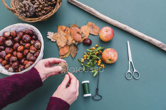 Close-up of female craftsperson hands preparing DIY autumnal decoration with natural materials — Stock Photo
