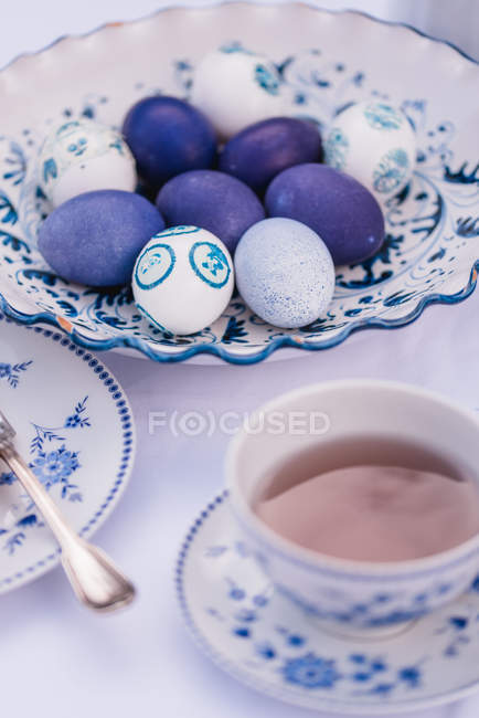 Easter table with eggs in blue and tea cup — Stock Photo