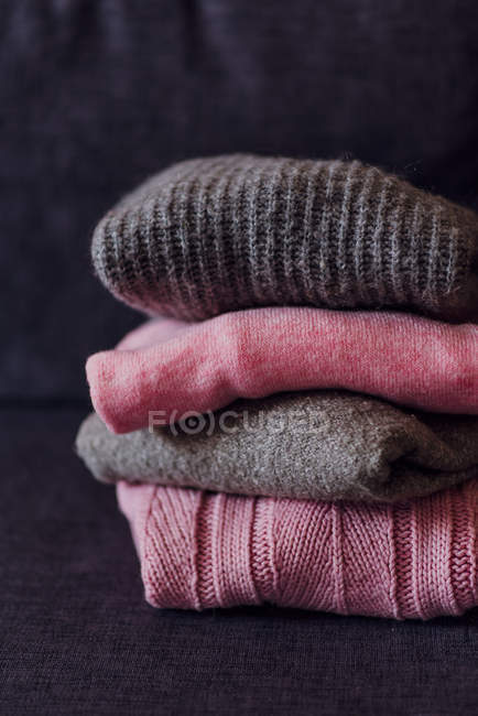 Stacked knitted pink and grey pullovers on sofa — Stock Photo