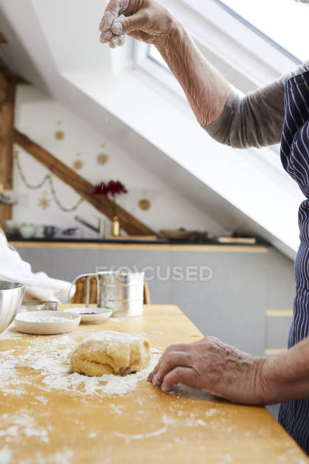 Cropped view of senior woman pouring cookie dough with flour in kitchen. — Stock Photo