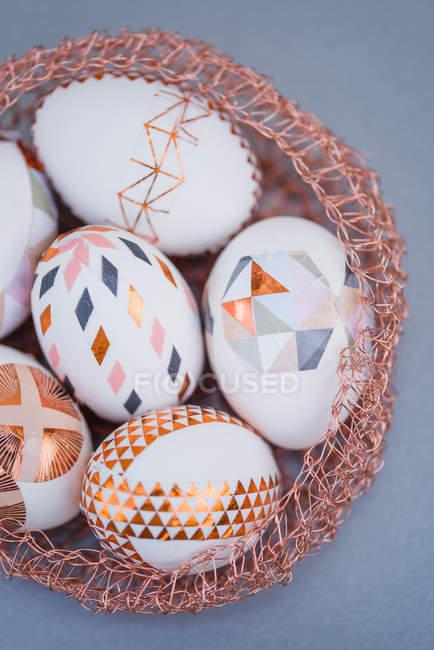 Primo piano delle uova di Pasqua dipinte geometriche nel nido decorativo su priorità bassa grigia — Foto stock