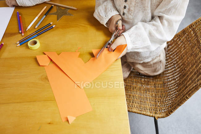 Cropped view of preschooler girl crafting paper Christmas star on table. — Stock Photo