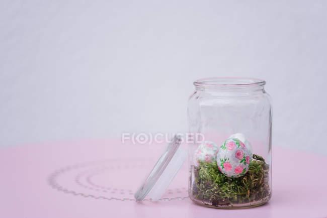 Оформлені писанок у jar на фоні сірих і рожевих — стокове фото