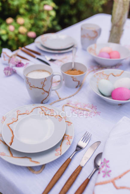 Setting table with easter decoration in garden — Stock Photo