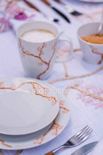 Covered table in spring mood with cutlery and porcelain tableware — Stock Photo