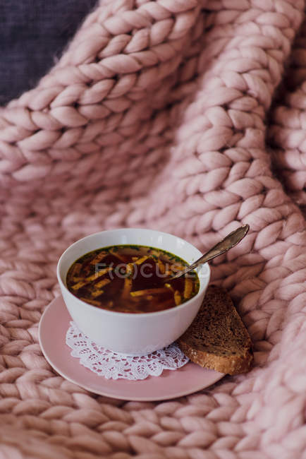 Sofa with knitted pink blanket and bowl of soup, close-up — Stock Photo