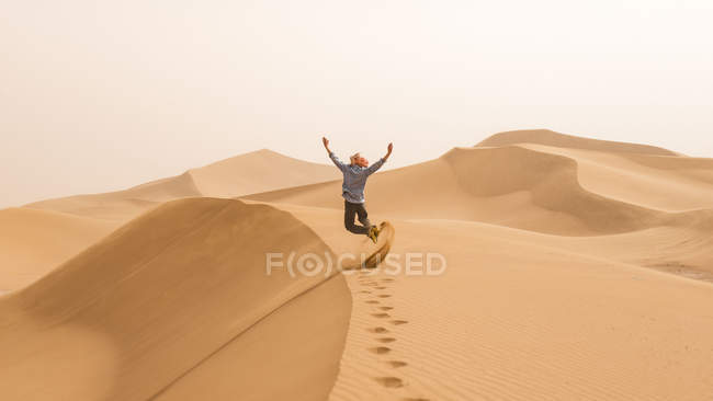 Person jumping on sand dunes of Sahara desert, Erg Chigaga, Morocco — Stock Photo