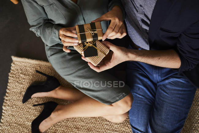 Cropped view of couple in love sharing presents at home at Christmas — Stock Photo