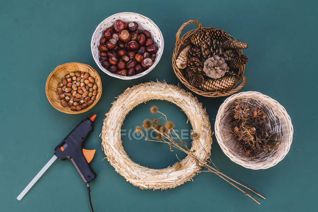 Still life of DIY straw wreath, nuts, chestnuts, cones, thistles and glue gun — Stock Photo