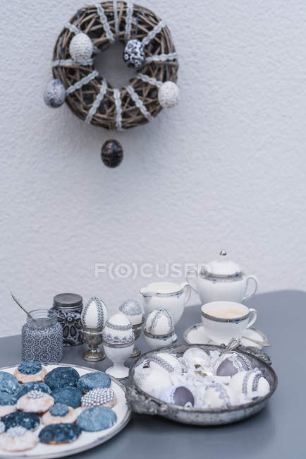 Table with Easter eggs and cookies for coffee service with wooden wreath on wall — Stock Photo