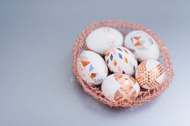 Uova di Pasqua dipinte geometriche nel nido decorativo su priorità bassa grigia — Foto stock