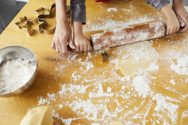 Cropped view of mother helping daughter rolling out dough for Christmas cookies. — Stock Photo