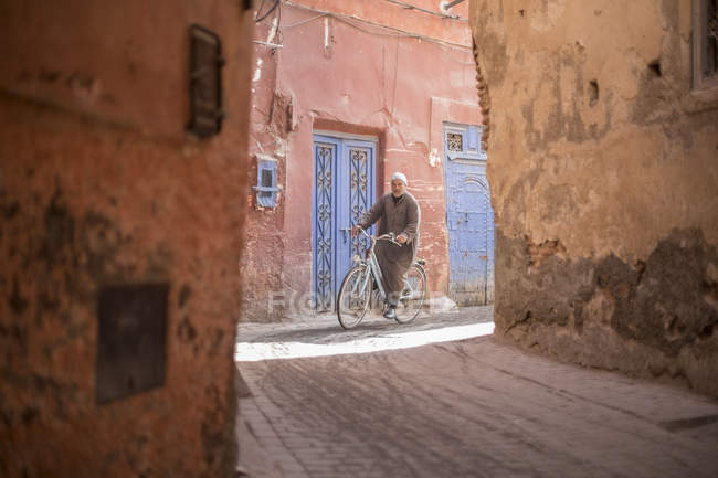 Street scene with local man on bicycle in ancient Marrakesh town, Morocco — Stock Photo
