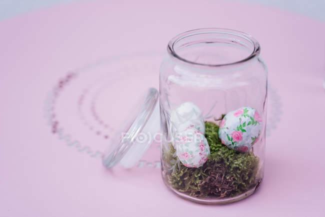 Великдень розписані яйця в банку на рожевий фон — стокове фото