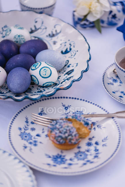 Easter table with colored eggs, muffin and tea cup — Stock Photo