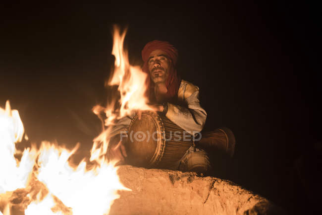 Bedouin playing drum at fireplace at night in Sahara desert, Erg Chigaga, Morocco — Stock Photo