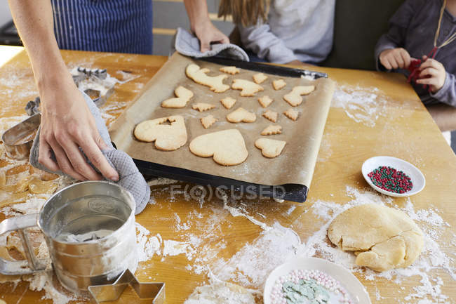 Cropped view of family putting Christmas cookies on baking tray. — Stock Photo