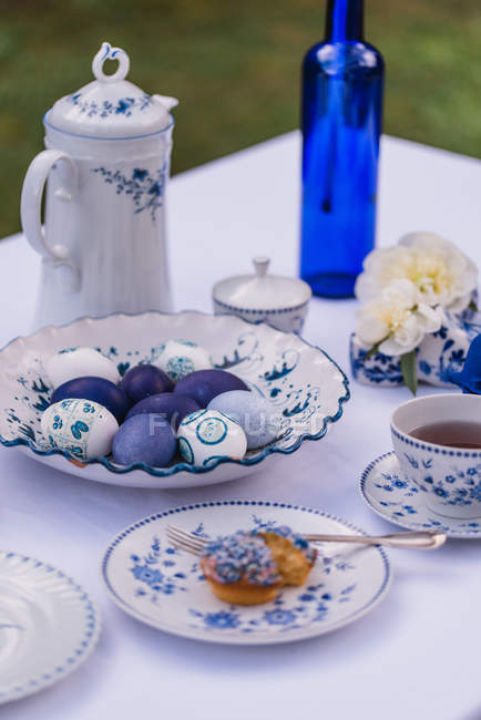 Easter table with eggs, muffin and tableware in blue — Stock Photo