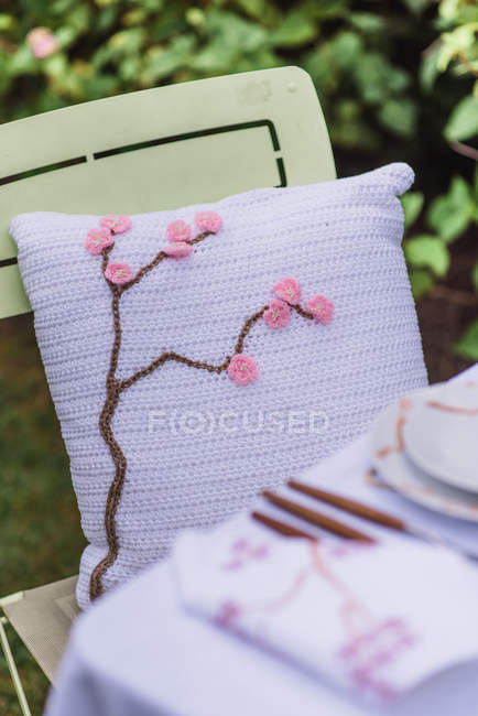 Outdoor furniture with cushion of spring mood by table — Stock Photo