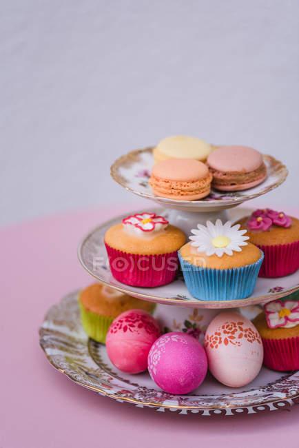 Decoração de ovos de Páscoa com macarons e muffins no carrinho de placas no fundo rosa — Fotografia de Stock
