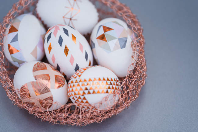 Closeup of geometrical painted Easter eggs in decorative nest on grey background — Stock Photo