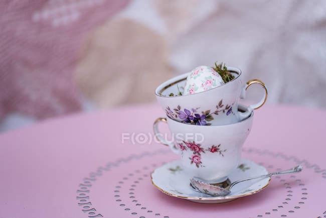 Діаграма з накопиченням vintage порцелянові чашки з пасхальне яйце на рожевий таблиці — стокове фото