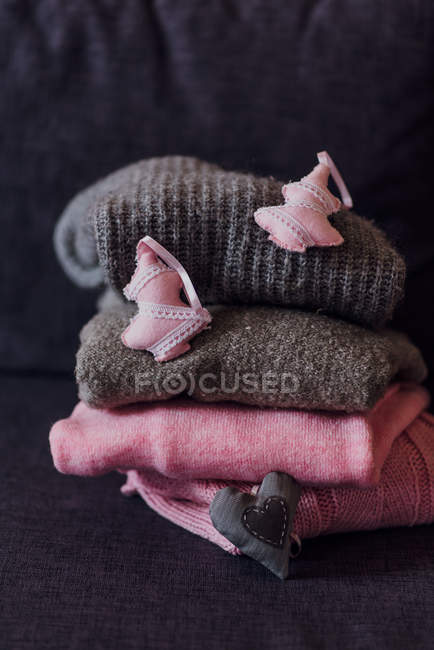 Stacked knitted pullovers with fabric tags on sofa — Stock Photo