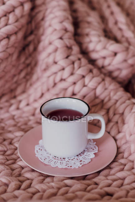 Sofa with pink blanket and teacup, close-up — Stock Photo