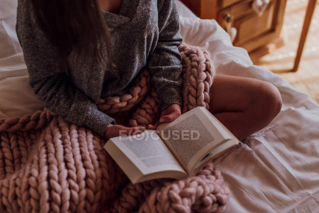 Cropped view of woman sitting in bed and reading book, detail — Stock Photo
